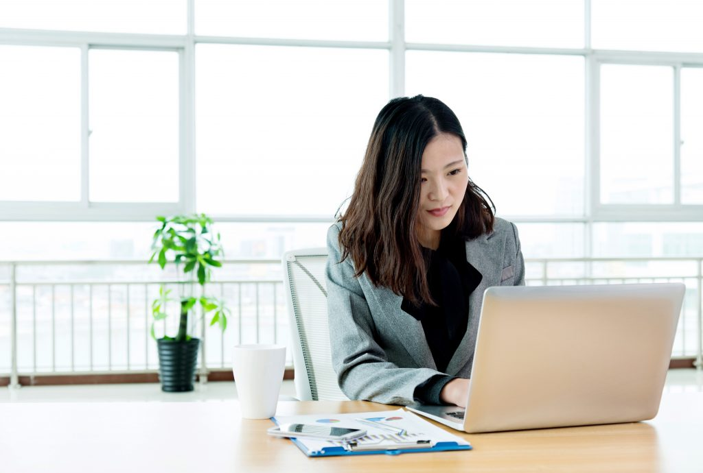 Young businesswoman working in the office with laptop.