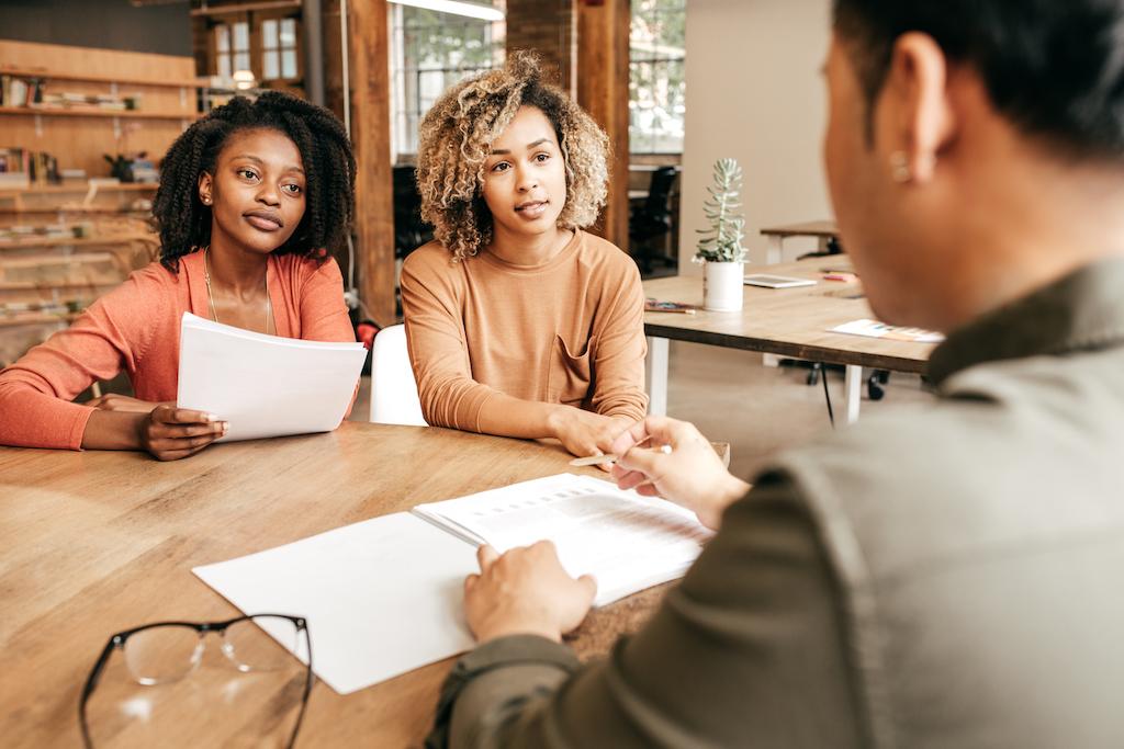 Three people around a desk, paperwork